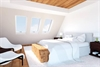 FAKRO z-wave white-paint triple glazed laminated centre pivot roof window in bedroom - Sterlingbuild